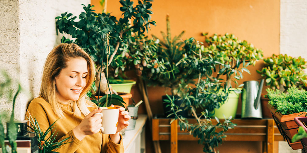 woman sipping tea on balcony with plants